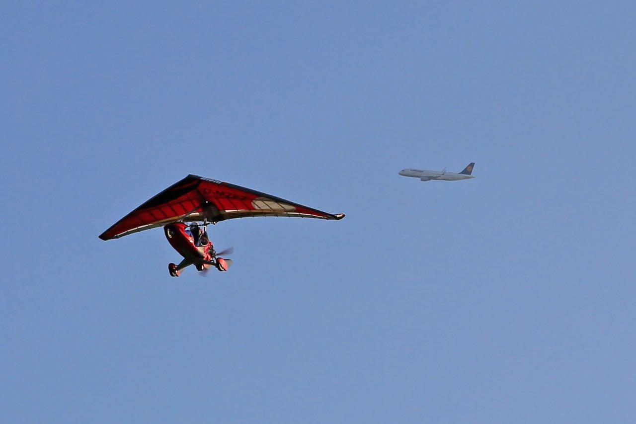 Trike von unten im Flug neben Airliner